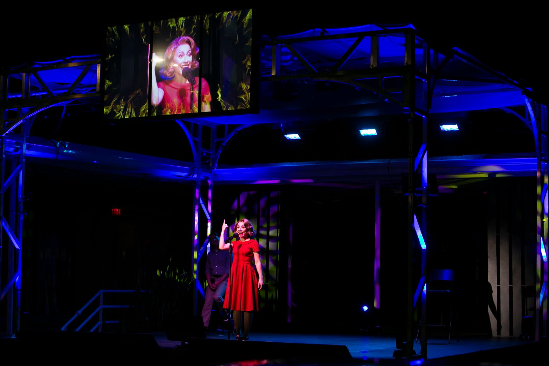 A woman performing in a red dress on a dark stage with a large screen image of her above it.