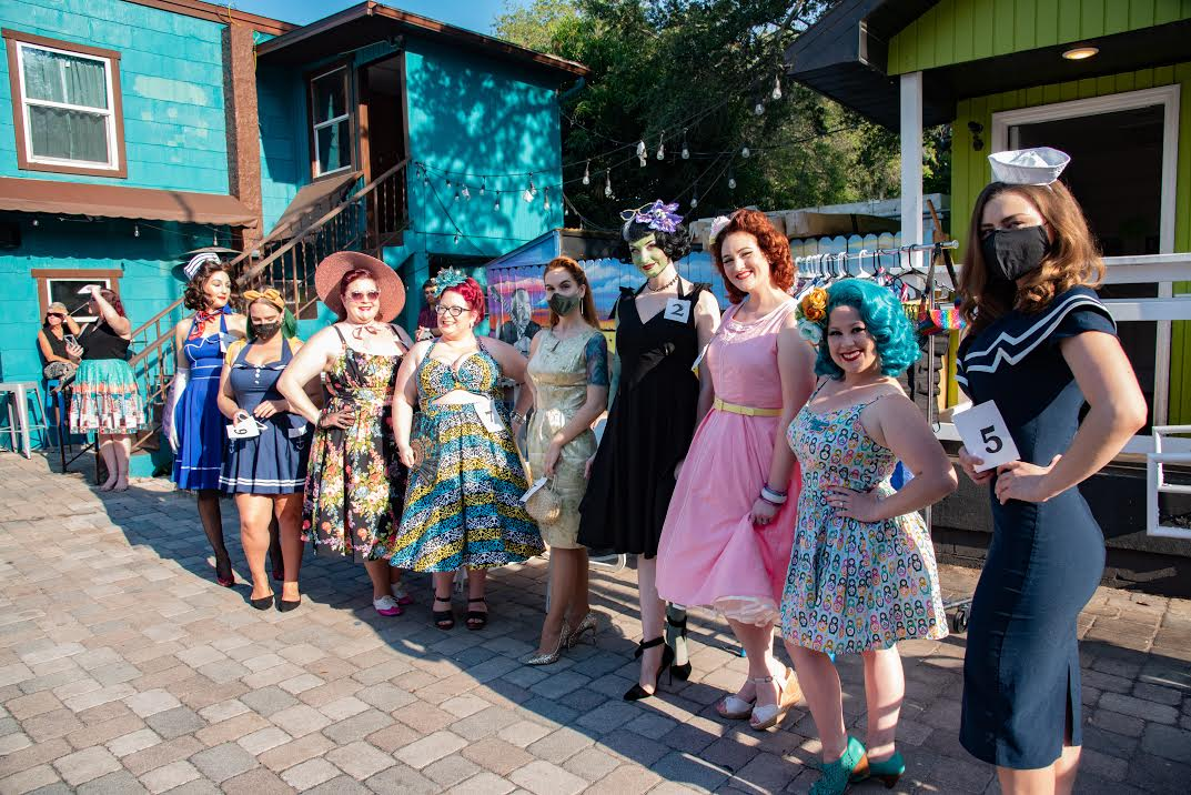 A line of women outside dressed in pinup costumes.