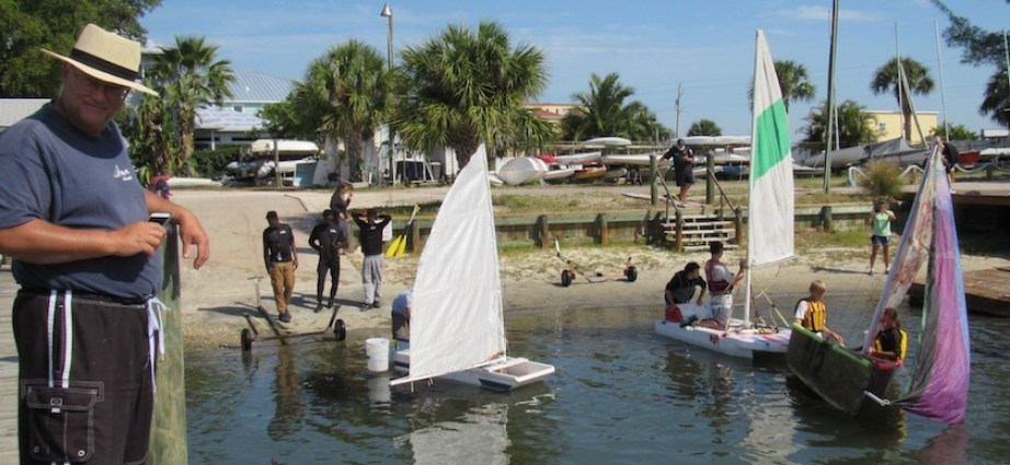A wide shot of people putting sail boats in the water as a man stands on a dock.