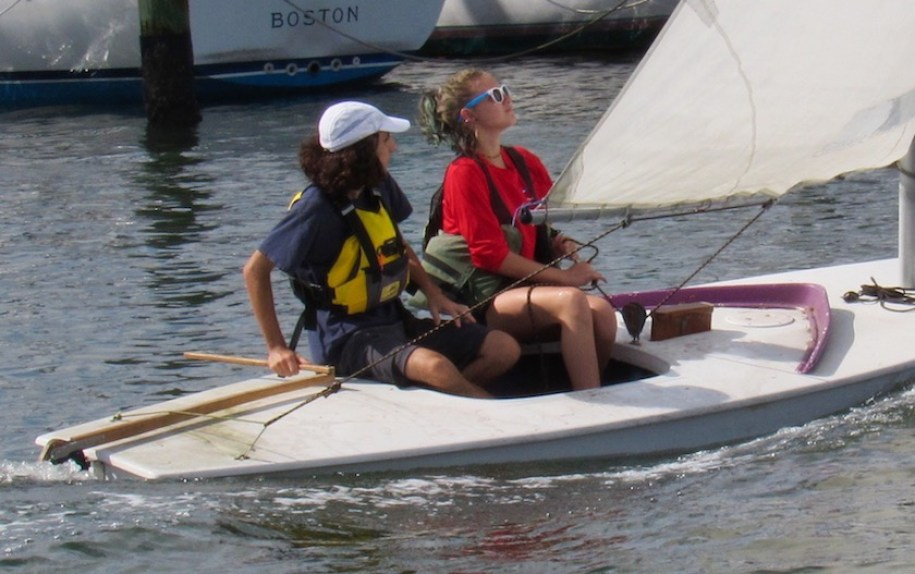 Two teens sailing a small boat with a white sail.