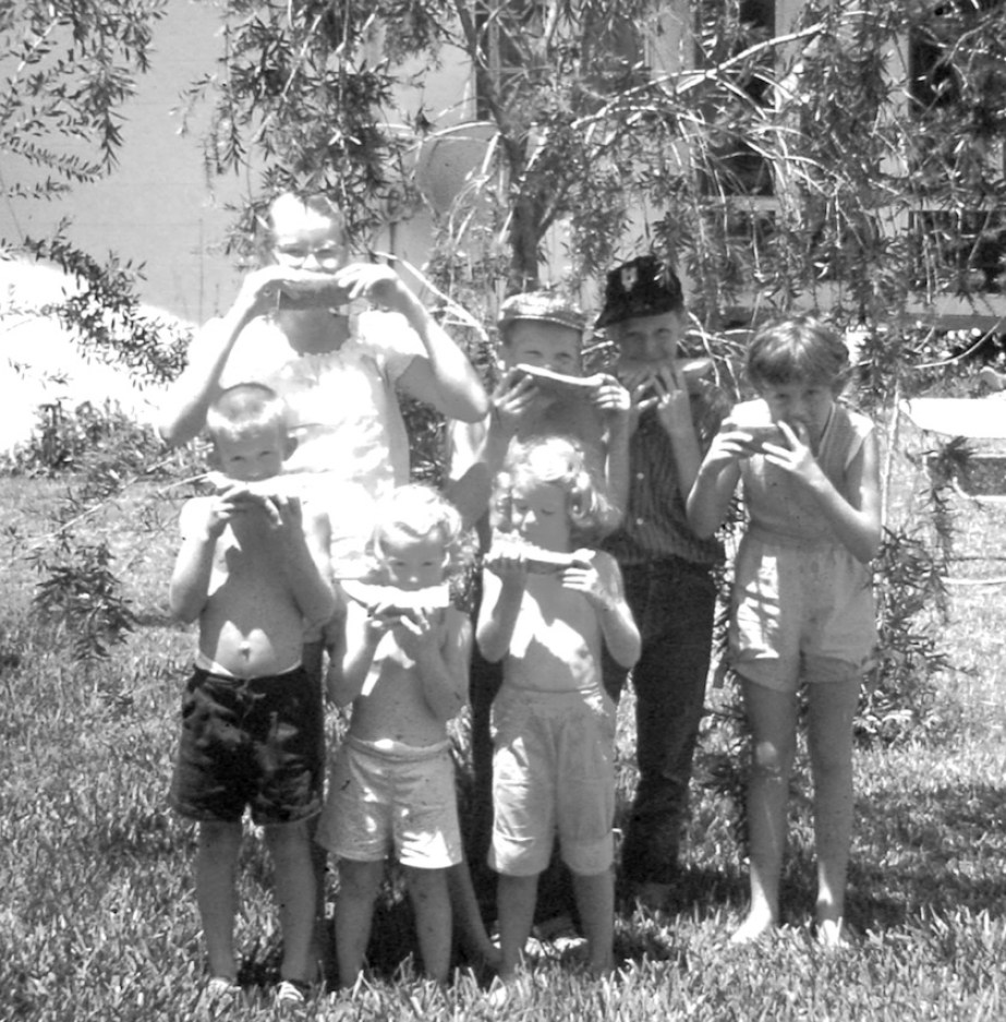 A black and white photo of children in a yard eating watermelon.