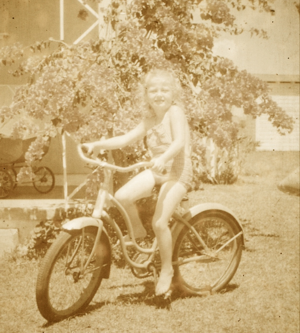 A sepia toned photo of a little girl on a bike.