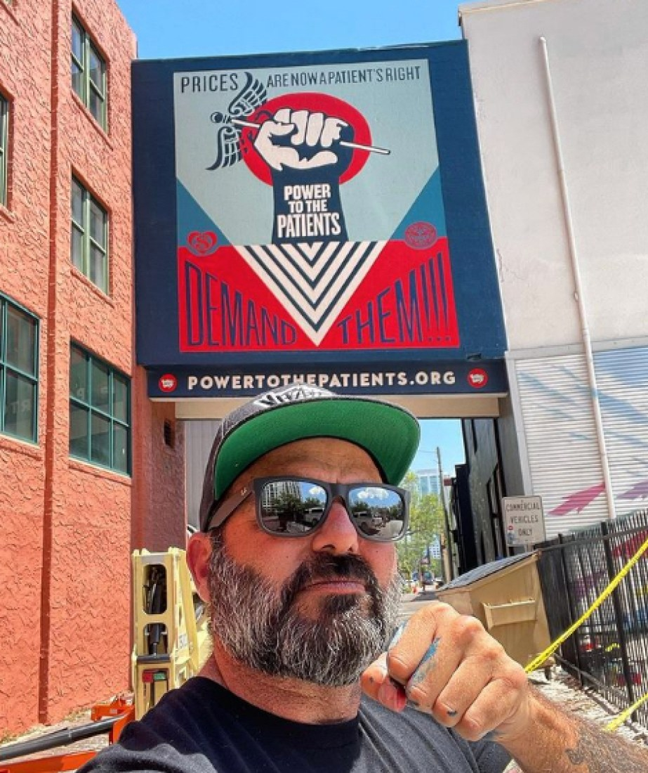 """A man with a ball cap, sunglasses and a beard standing in front of a mural of a raised fist that reads """"Prices are now a patient's right""""; Power to the patients; Demand them; Powertothepatients.org"""""""