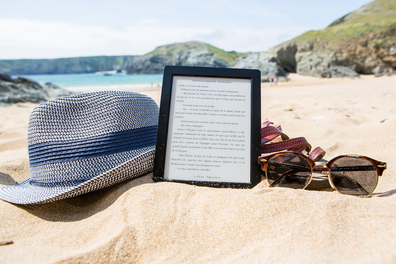 Ebook hat and sunglasses sitting in the sand at a beach.