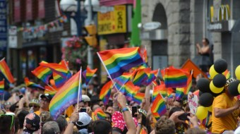 People raising their rainbow flags in a Pride parade.