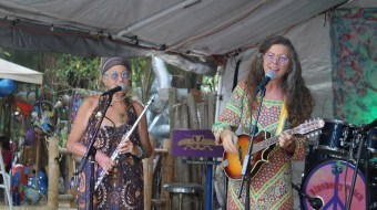 Two women in hippie style clothes on a stage with a flute and a guitar.