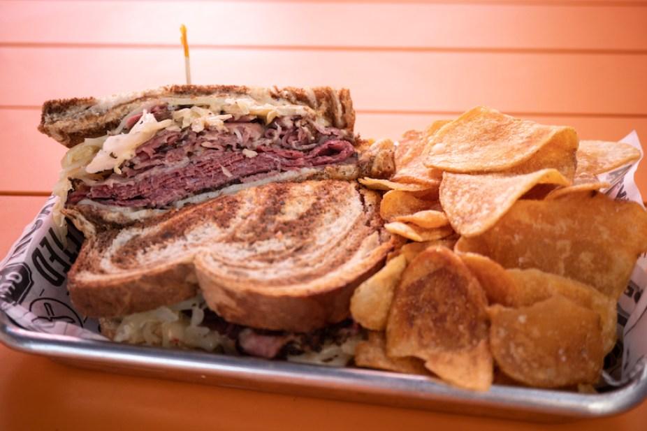 A photo of a Rueben sandwich and potato chips.