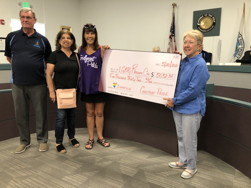 A man and three women stand with a large ceremonial check  for $5,032.62