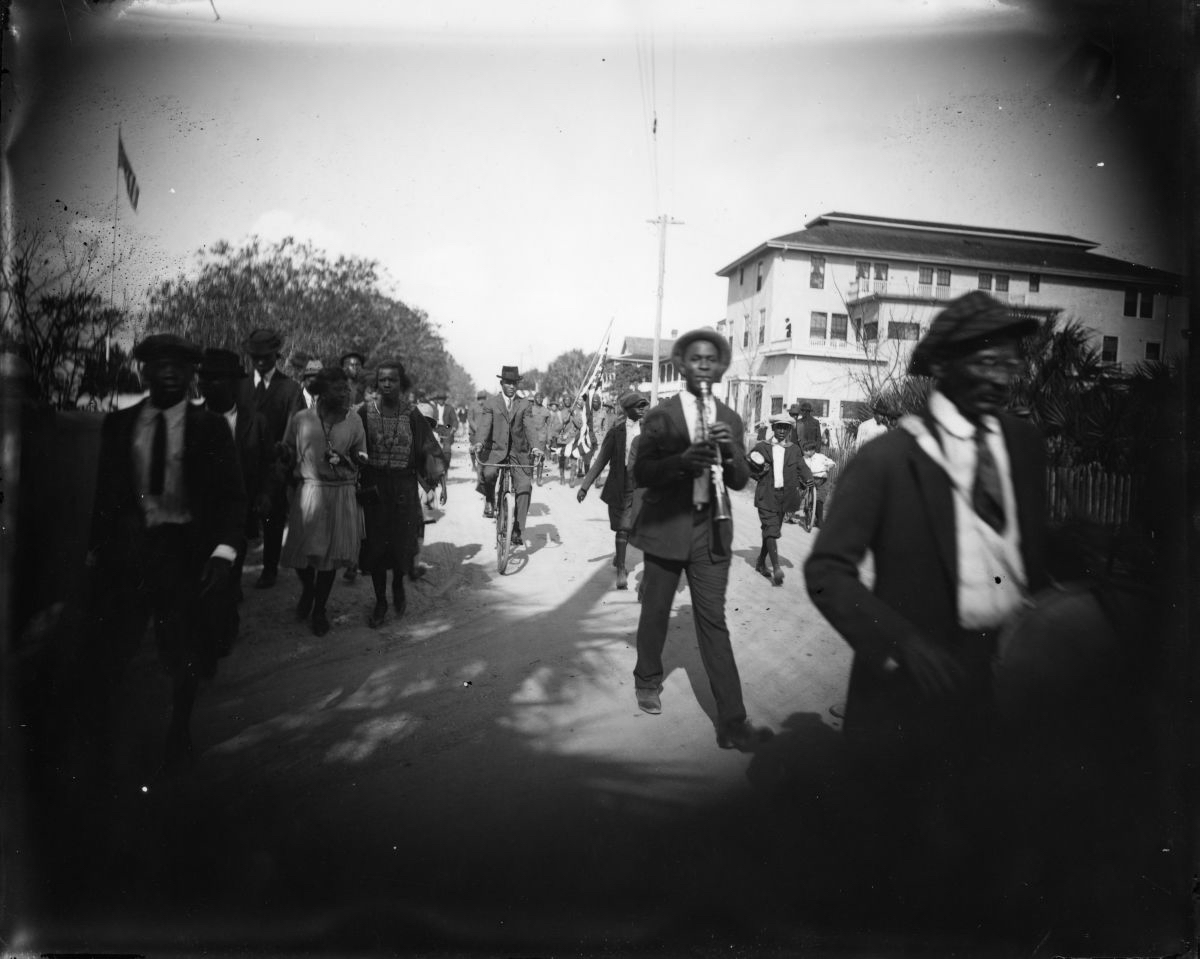 A black and white photo of men in suits marching in a parade.