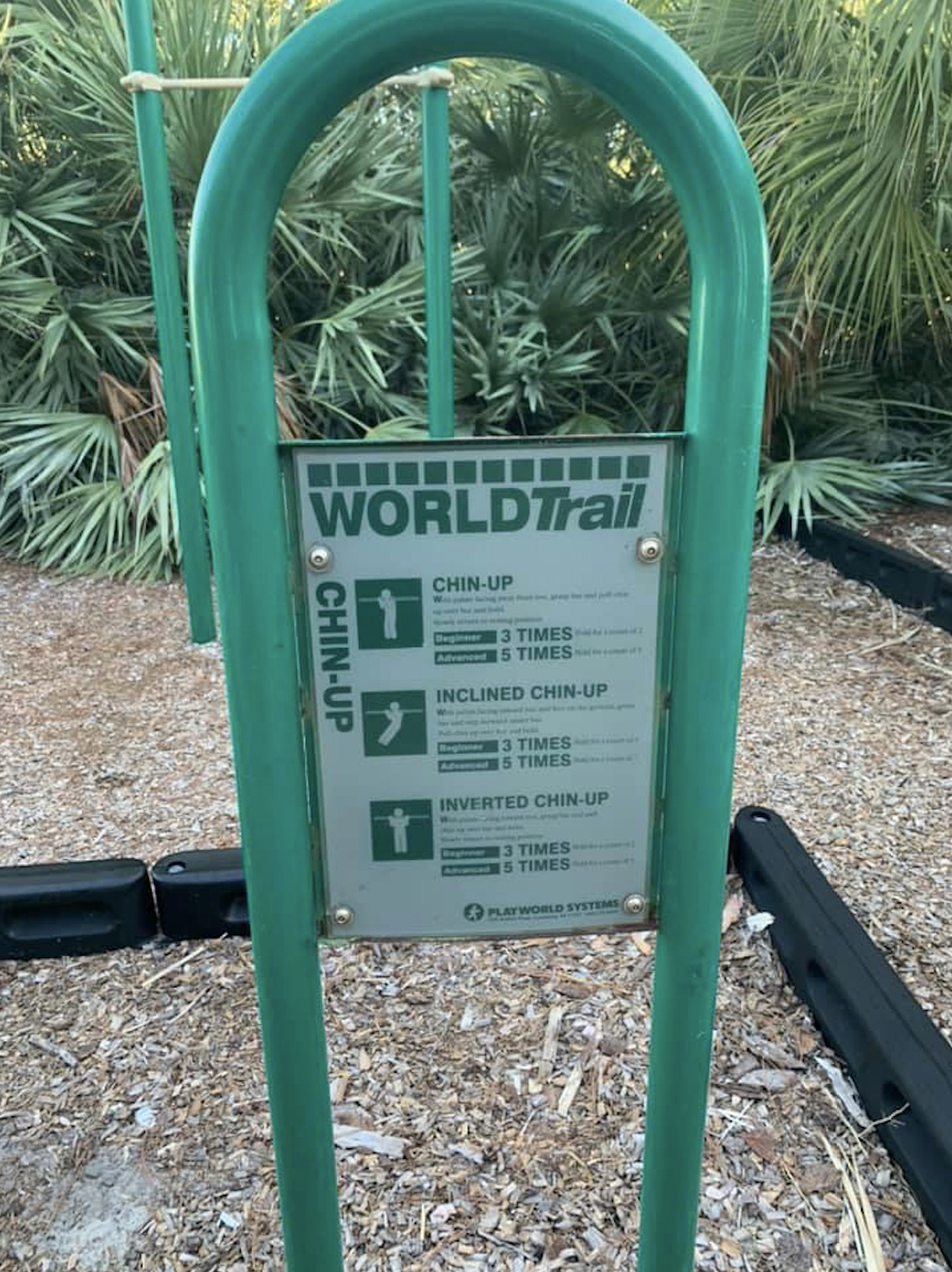 """A photo of a green sign in a park that reads """"World Trail"""" with exercise activities."""