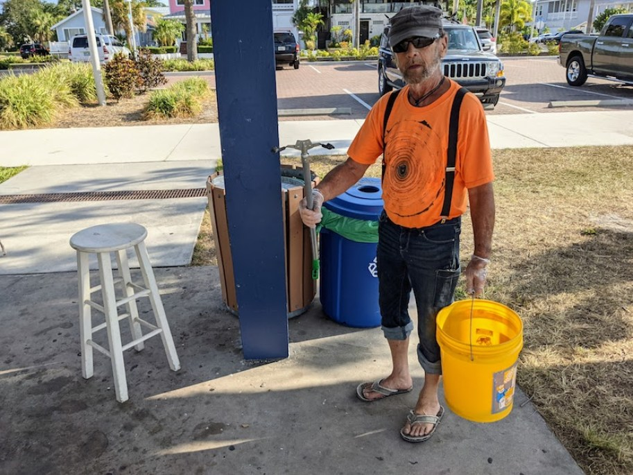 A man in an orange shirt and sunglasses with a yellow bucket and trash picker at a beach pavilion.