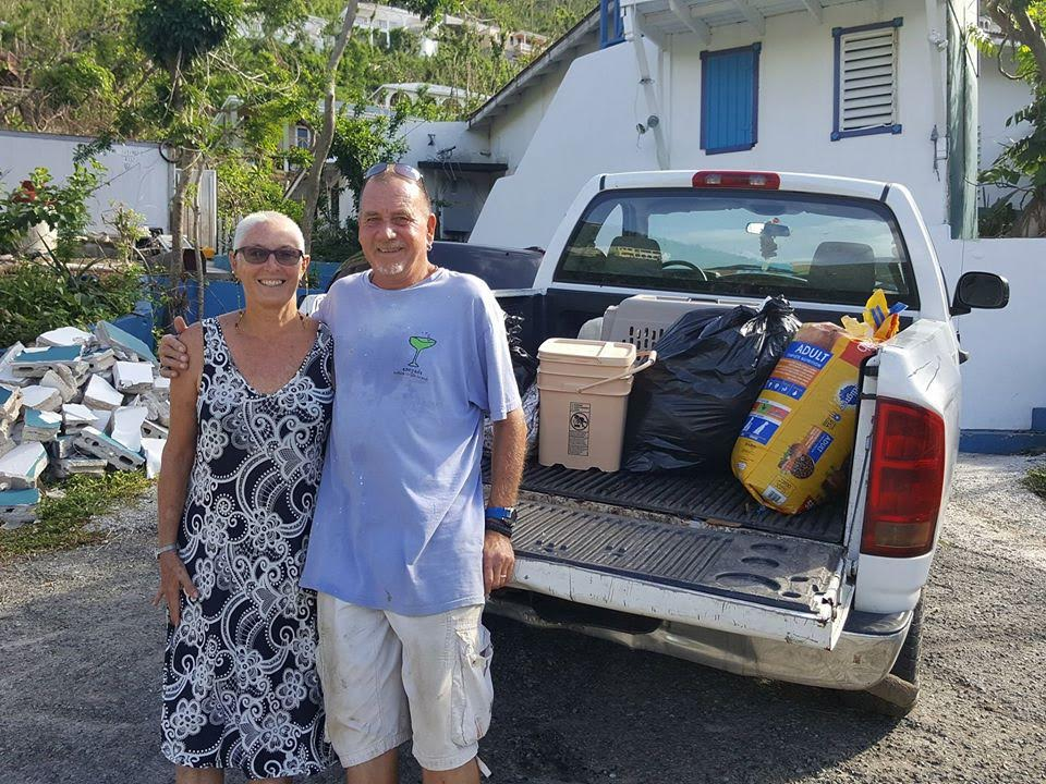 A man and a woman with their arms around each other looking at the camera in front of a truck bed with supplies in it.