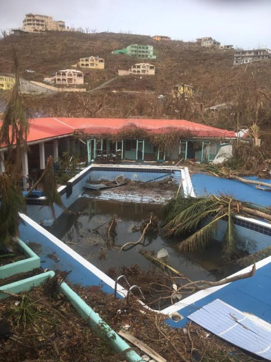 A scene of destruction at a small hotel after a hurricane with an empty swimming pool.