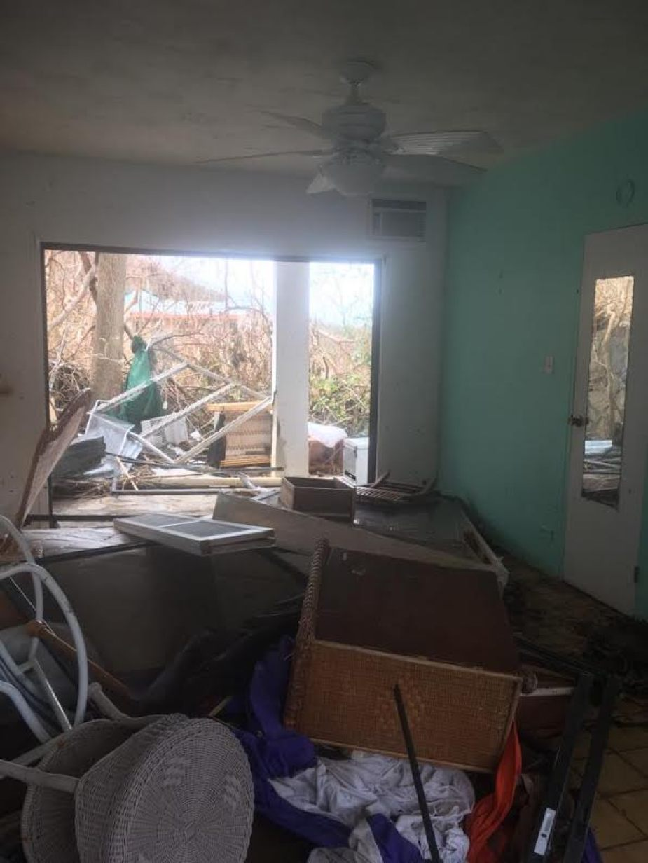 A photo of a room with flooding and debris after a hurricane.