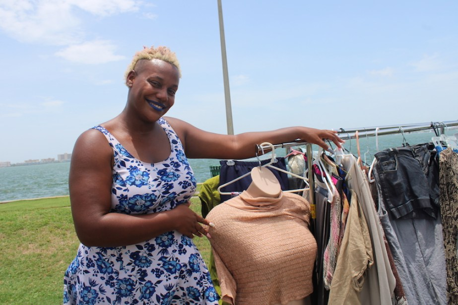 A photo of a woman in a blue floral print dress showing off a display of clothing outside.