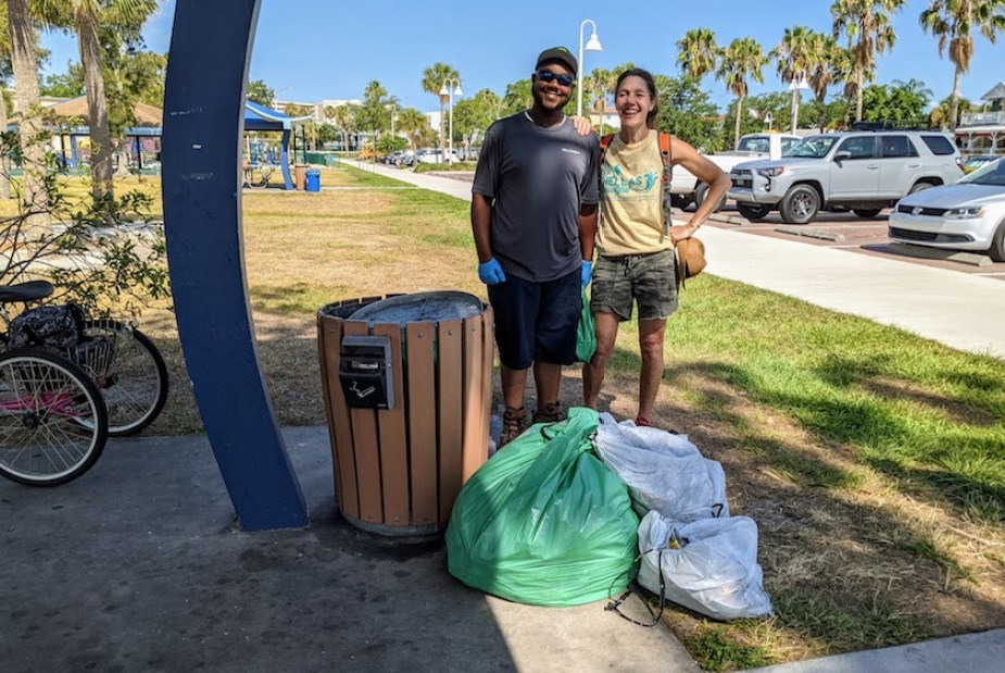 Two people at a pavilion on a beach with a large green bag of trash.