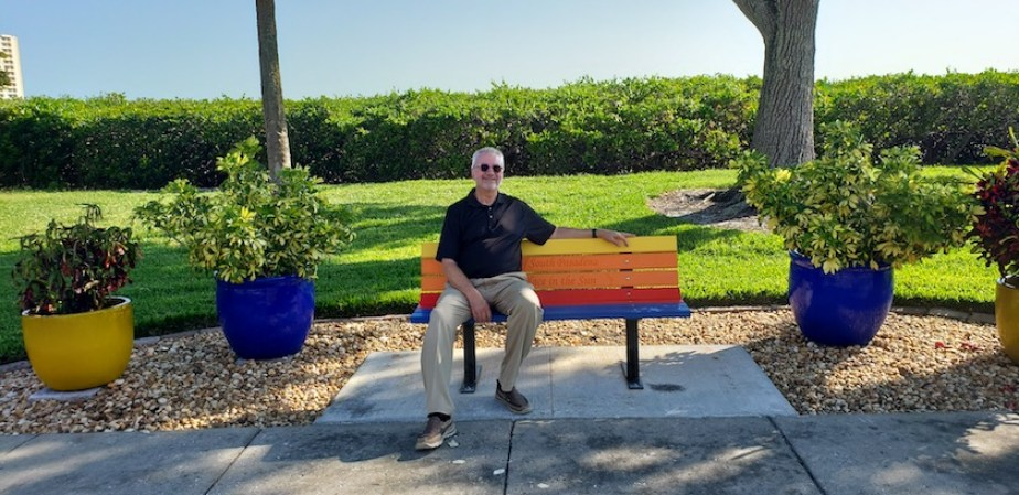 A man sitting on a colorful bench outdoors in the sunshine.