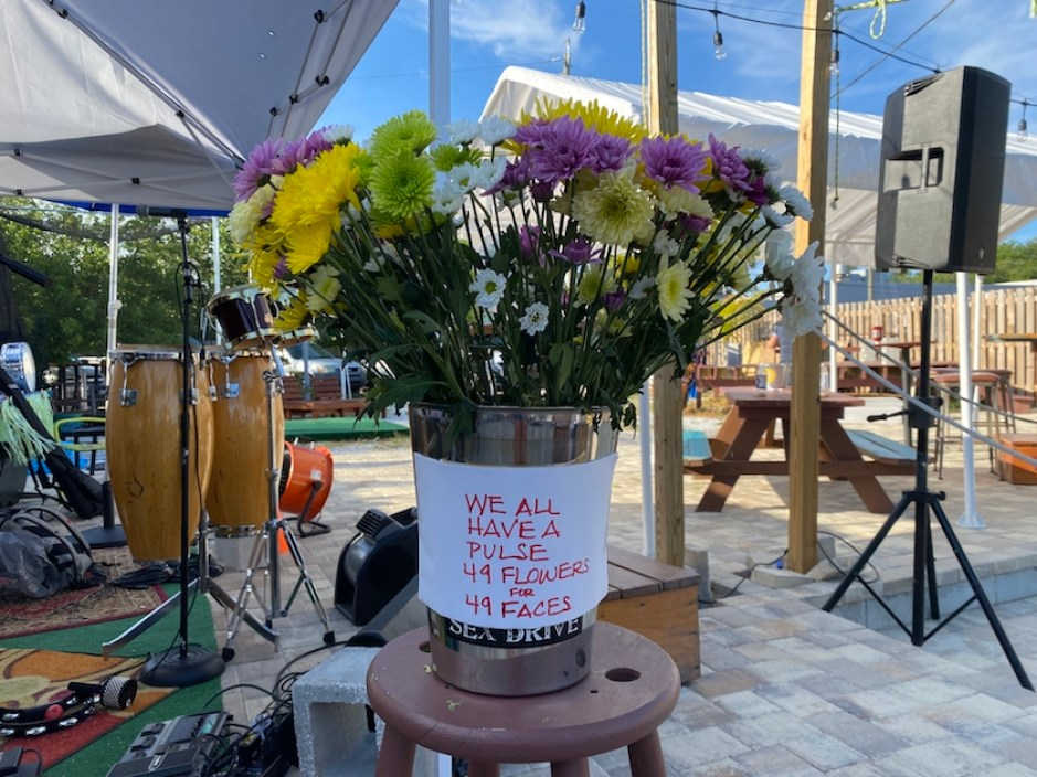 """A bucket of flowers with a sign that reads """"We all have a pulse. 49 Flowers for 49 Faces."""""""