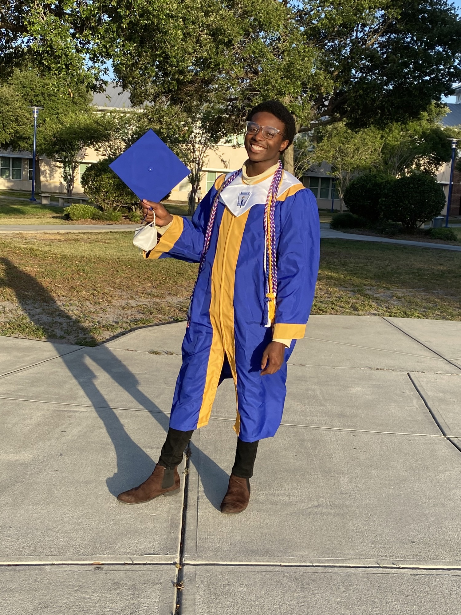 A young man in blue and gold graduation robes holding his mortarboard hat.