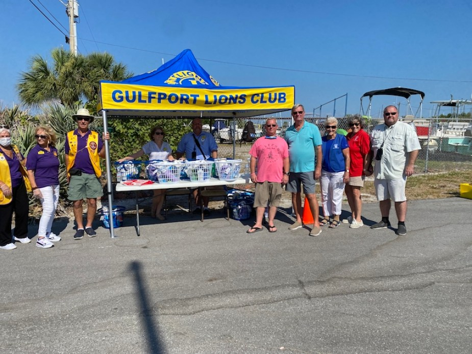 """A photo of people outside by a table with a sign that reads """"Gulfport Lions Club"""""""