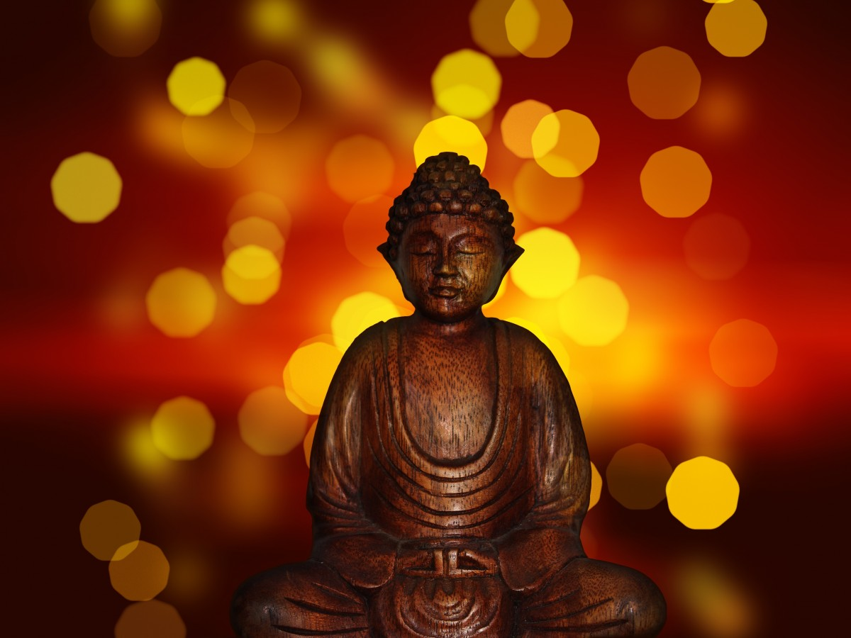 Buddha statue against glimmering lights
