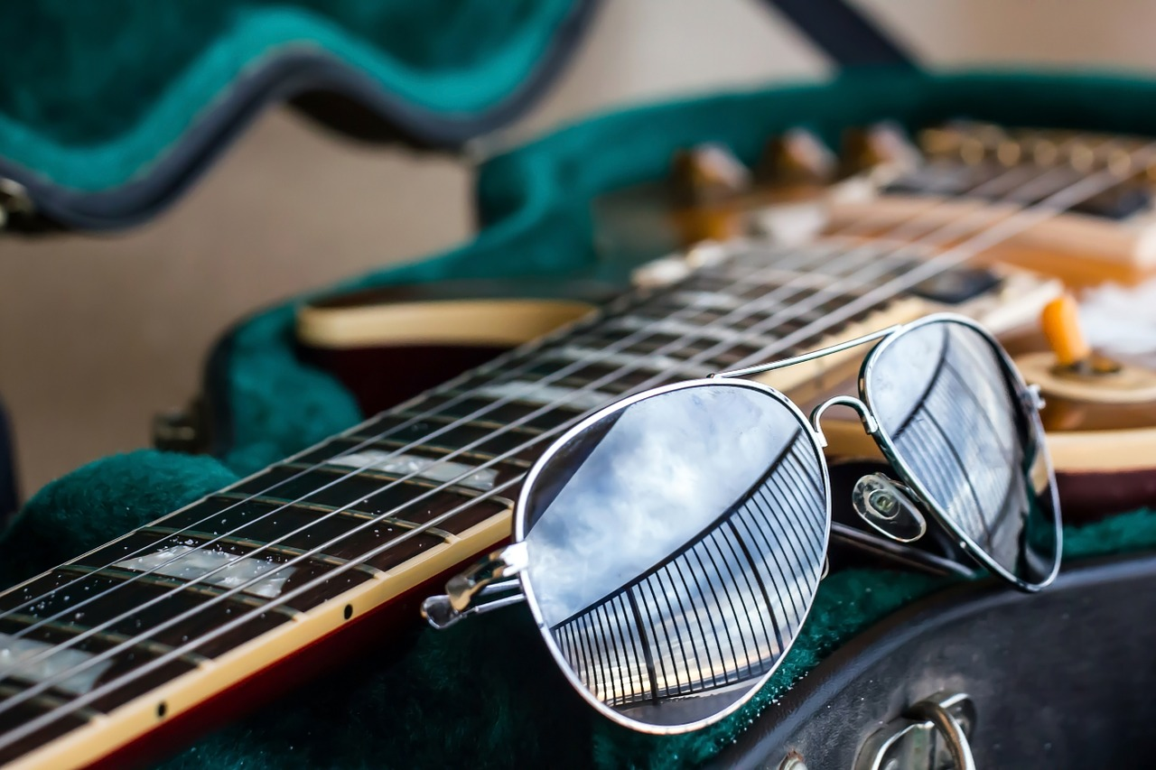 A close up photo of aviator sunglasses and the neck of a guitar.