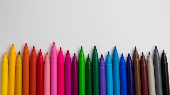 Colored pencils lined up in front of white screen