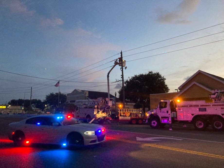 A photo of a street scene at sunset with workers clearing the scene of a car accident with a white police car with blue and red lights on in the foreground.