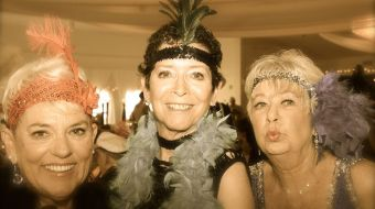Three women in hats and beads smiling with an old-timey filter