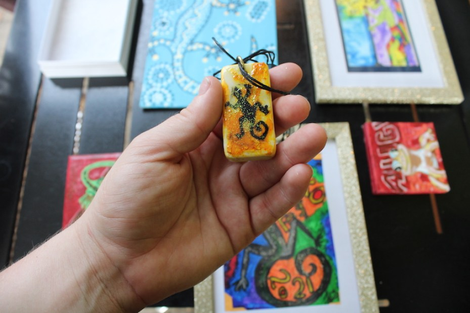 A hand holding a small rectangular pendant with a gecko painted on it, over a grouping of framed and canvas art pieces.
