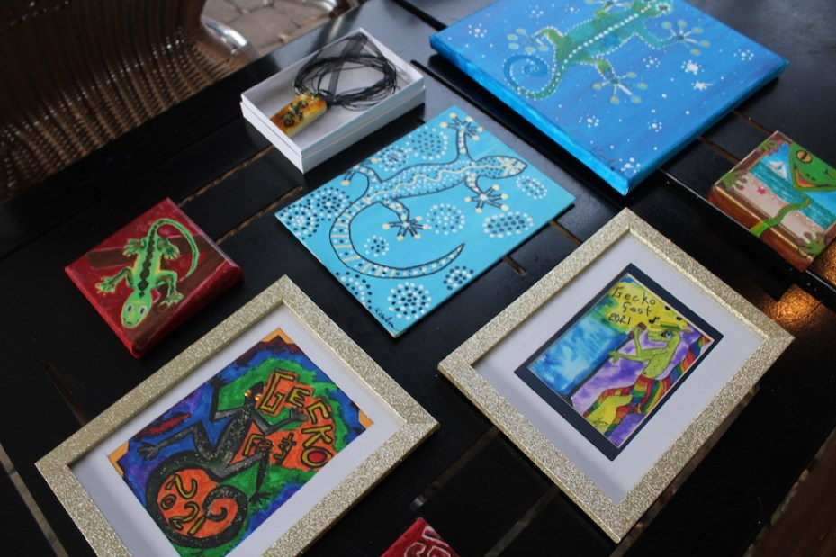a grouping of framed and canvas art pieces on a black table top.