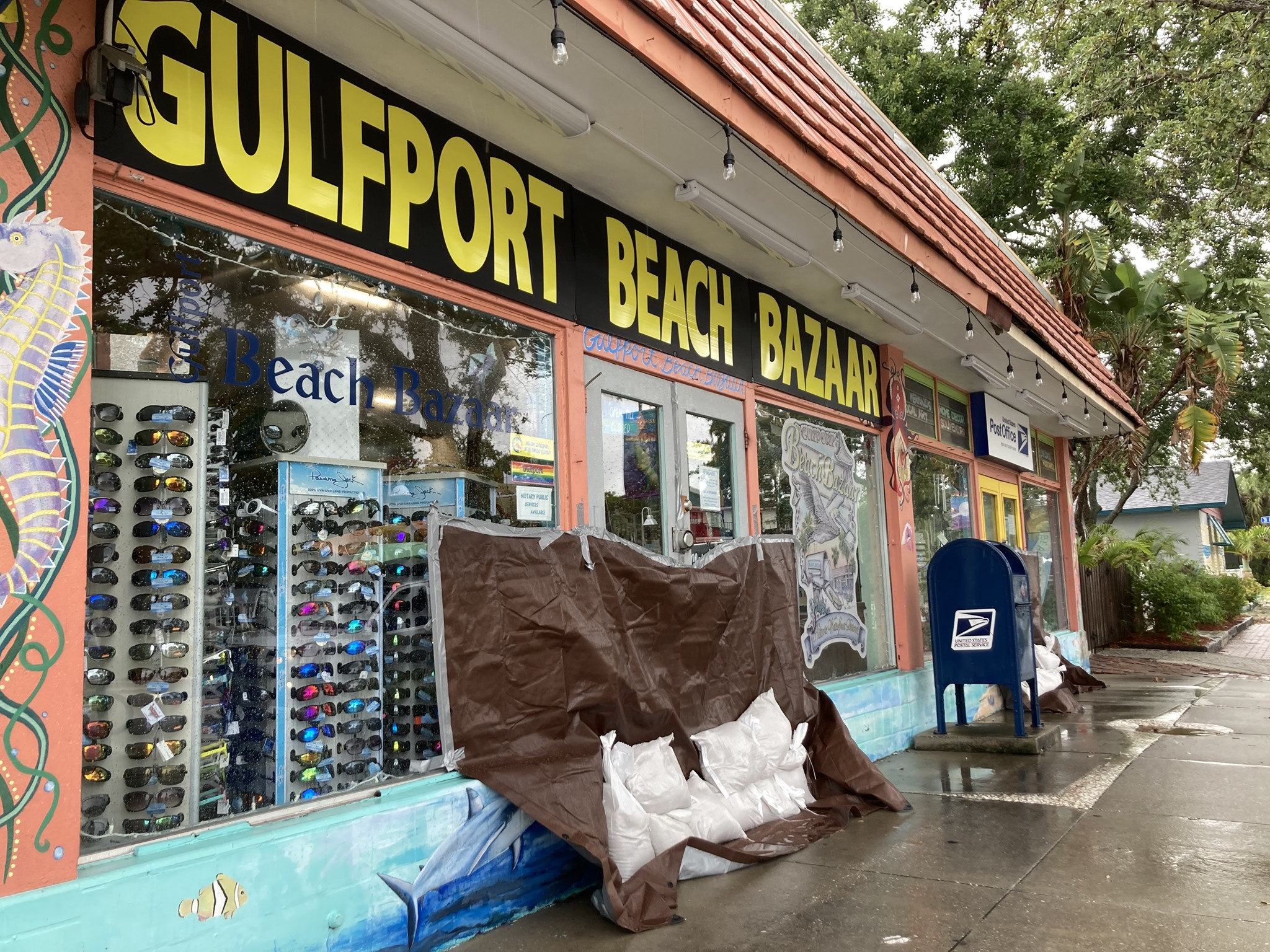 """A shop front with a sign that reads """"Gulfport Beach Bazaar"""" with the doorway trapped up and sandbagged."""