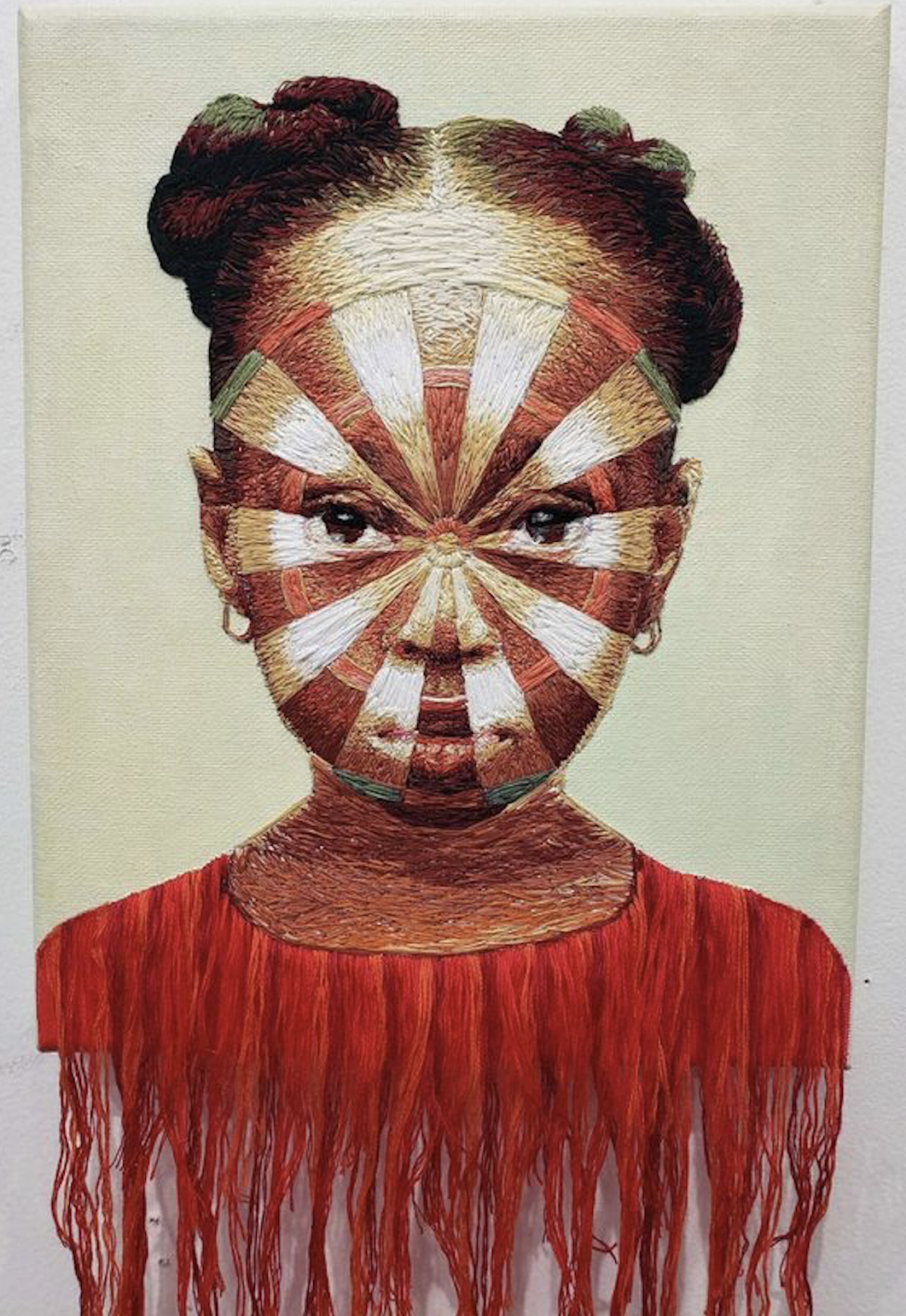 A painting of a little girl in a red shirt with a dart board superimposed over her face.