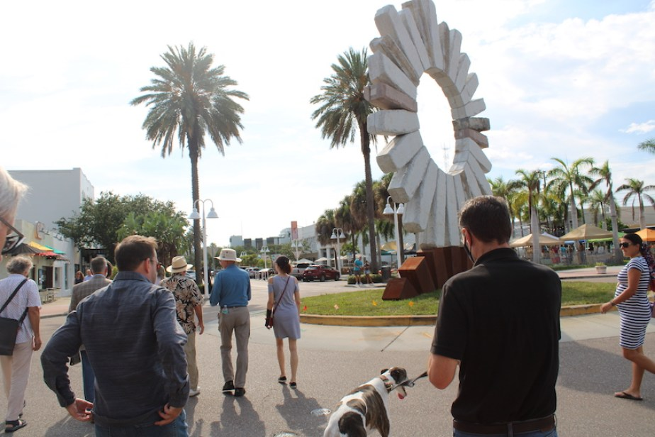 A photo of people walking on a street with palm trees in front of a giant stone sun sculpture outside.