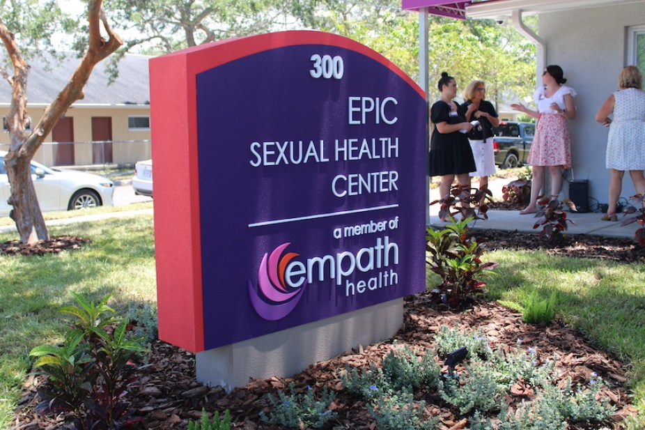 """A purple and pink sign that reads """"EPIC Sexual Health Center; Empath"""" in white letters with people in the background."""