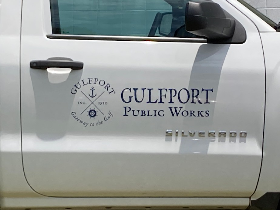 """A photo of the door of a white truck with a logo and the words """"Gulfport Public Works"""" written on it."""