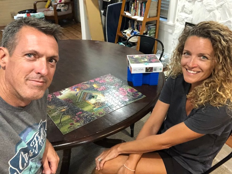 A man and a woman sitting at a table with a puzzle smiling at the camera.