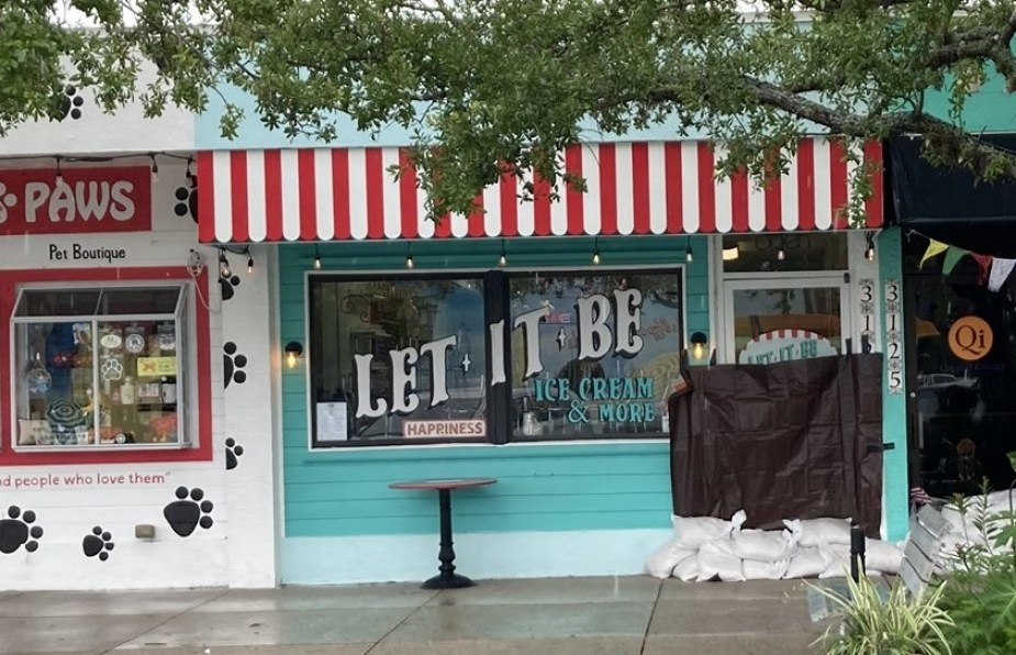 """A shop front with a sign that reads """"Let It Be"""" with the doorway trapped up and sandbagged."""