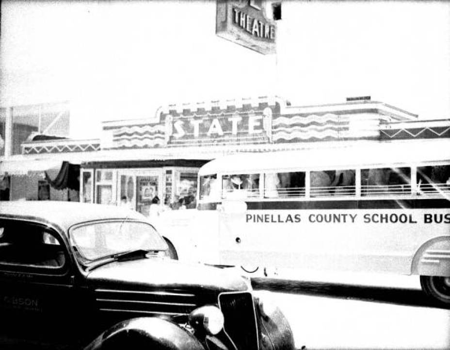An old black and white photo of a school bus passing a 1940s car on a street.