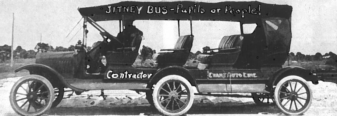 """An old photo of an extra long early 1900s car with the words """"Jitney Bus"""" on the top."""