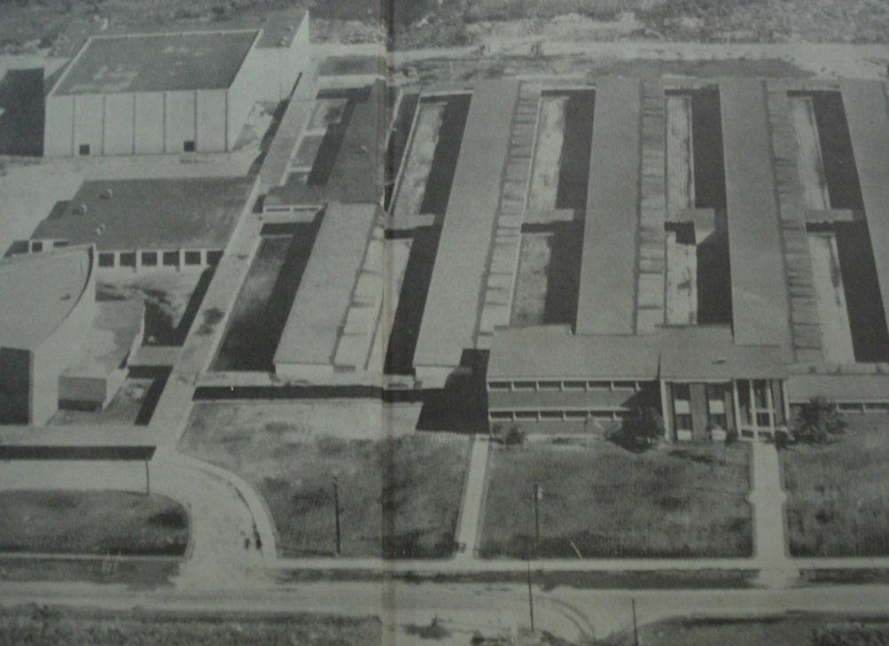 An old black and white photo of an aerial shot of a high school with groups of buildings.