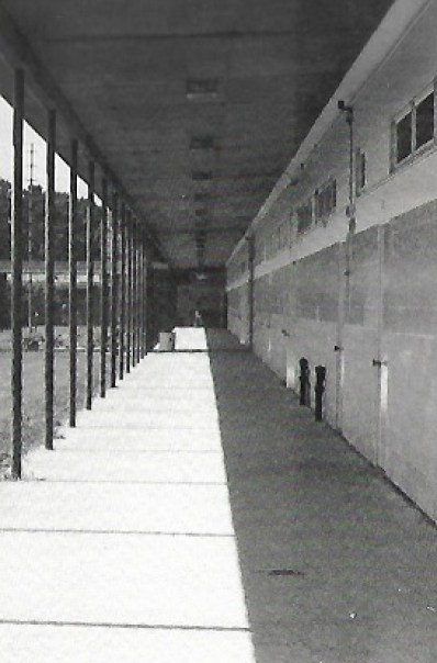 An old black and white photo of an open-air hallway at a school.