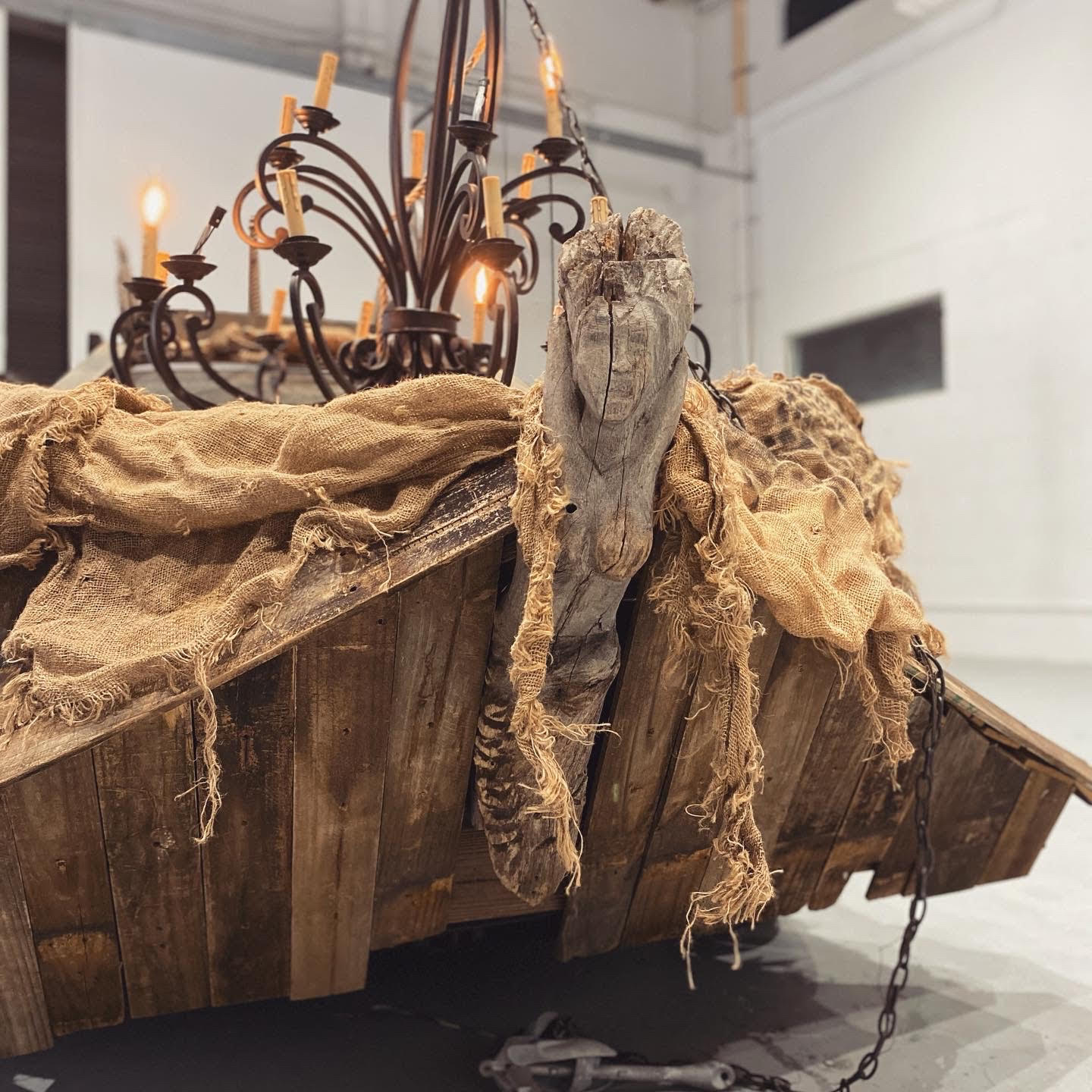 A photo of a wooden art piece with a chandelier over it, dropped in burlap cloth and the head of a woman figure on the side.