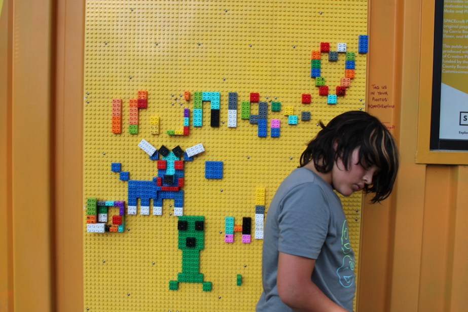 A kid playing with a big yellow leg wall.