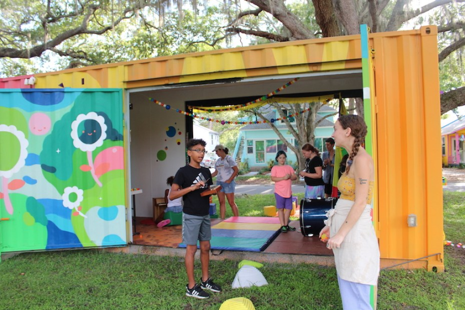 A shipping container repurposed into a art learning space in a park. with two people talking in front of it.