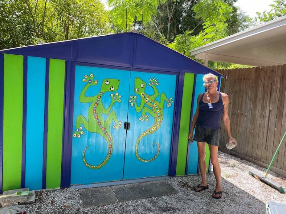 A woman in a tank top and shorts standing next to a painted in blue and green with colorful geckos painted on the doors.