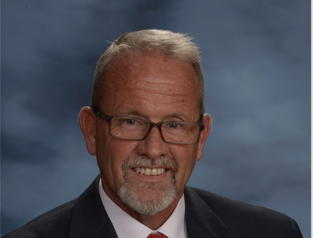 A head shot of a man in a dark suit, red tie and an American flag pin.