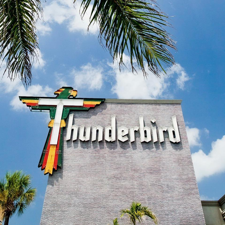 A photo of the from sign for the Thunderbird hotel with blue sky and palm fronds.