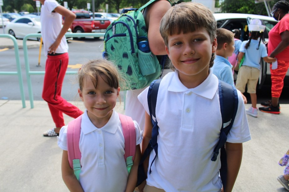 A young girl and a young boy smiling at the camera wearing backpacks outside a school.