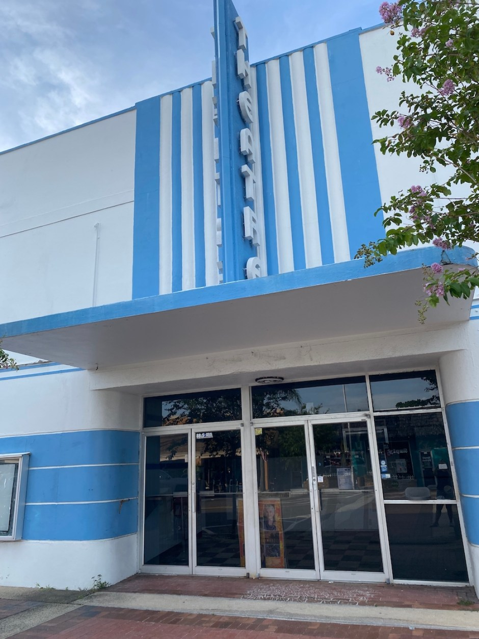 A photo of a building with double doors and blue and white striping above them.